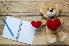 Teddy bear holding a heart-shaped pillow Stock Images