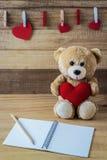 Teddy bear holding a heart-shaped pillow Stock Photos