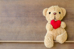 Teddy bear holding a heart-shaped pillow. On wood shelf board background Royalty Free Stock Photo