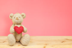 Teddy bear holding heart on wood table on pink background Royalty Free Stock Image