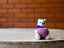 Teddy bear holding a purple heart. Placed on a wooden desk. Royalty Free Stock Photo