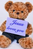 Teddy bear holding a purple sign that says Jesus loves you royalty free stock photo