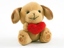 Teddy bear holding a red heart. Little plush puppy dog or Teddy bear holding (giving) a red heart stock photos