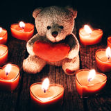 Teddy bear holding red heart. Teddy bear holding a heart on a woody background Stock Photo
