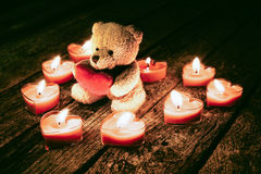 Teddy bear holding red heart. Teddy bear holding a heart on a woody background Royalty Free Stock Photography