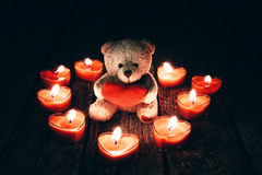 Teddy bear holding red heart. Teddy bear holding a heart on a woody background Stock Image