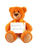 Teddy Bear. Holding a sheet of paper with greeting inscription Happy Birthday.  on a white background Stock Image