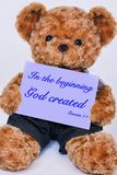 Teddy bear holding a sign that says In the beginning God create royalty free stock images