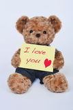 Teddy bear holding a  yellow sign Stock Photography