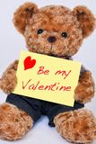 Teddy bear holding a yellow sign that says Be my Valentine isola. A cute teddy bear holding a yellow sign that says Be my Valentine isolated on a white Royalty Free Stock Images