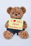 Teddy bear holding a yellow sign that says I love mom isolated on white background Royalty Free Stock Photo