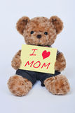 Teddy bear holding a yellow sign that says I love mom Royalty Free Stock Images