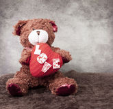 Teddy bear holds in paws heart symbol . Royalty Free Stock Photos