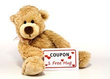 Teddy bear with hug coupon. Cute furry brown teddy bear sitting and holding a coupon for one free hug  on white background with copy space Stock Photo