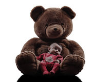 Teddy bear hugging baby sitting silhouette Stock Photos