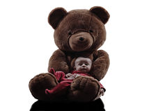 Teddy bear hugging baby sitting silhouette Stock Photos