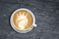 Teddy bear latte art coffee cup on textured black shist with obl stock photography