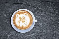 Teddy bear latte art coffee cup on textured black shist with obl royalty free stock photography