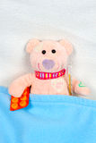 Teddy bear laying in bed with thermometer Stock Photo