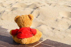 Teddy bear left alone on the beach  in a sunny day Stock Photos