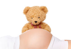 Teddy bear looking at belly of a pregnant woman Royalty Free Stock Photos