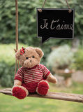 Teddy bear in love. A teddy bear on a swing that sends a message of love Royalty Free Stock Photos
