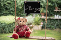Teddy bear in love. A teddy bear on a swing that sends a message of love Stock Photos