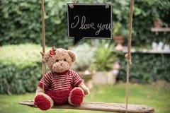 Teddy bear in love. A teddy bear on a swing that sends a message of love Stock Photos