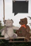 Teddy bear in love. Two teddy bears on a swing with a blackboard where you can write a message of love Royalty Free Stock Photo