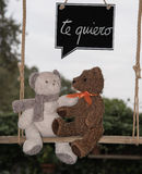 Teddy bear in love. Two teddy bears on a swing with a message of love Stock Photo