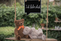 Teddy bear in love. Two teddy bears on a swing with a message of love Royalty Free Stock Photography