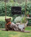 Teddy bear in love. Two teddy bears on a swing with a message of love Stock Photos