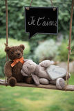 Teddy bear in love. Two teddy bears on a swing with a message of love Royalty Free Stock Images