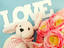 Teddy bear with love word and artificial roses flower with pink background Stock Image