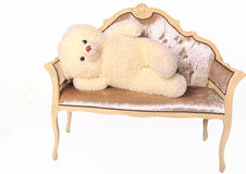 Teddy bear lying on a bench. N a white background Royalty Free Stock Photos