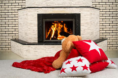 Teddy bear lying on the pillow,covered with a blanket and watching the flames of the fire in the fireplace. Teddy bear lying on the pillow,covered with a stock photography