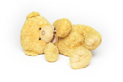 Teddy bear lying. Soft plush cute yellow teddy bear is lying on it's side looking upset, on white Royalty Free Stock Photography