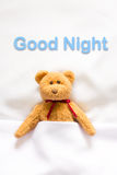 Teddy Bear lying in the white bed with message ' Good night '.  Stock Photos