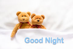 Teddy Bear lying in the white bed with message ' Good night '.  Royalty Free Stock Photography