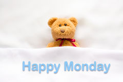 Teddy Bear lying in the white bed with message ' Happy Monday '.  royalty free stock image