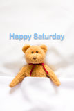 Teddy Bear lying in the white bed with message ' Happy Saturday' Royalty Free Stock Image