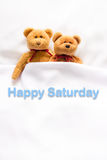Teddy Bear lying in the white bed with message ' Happy Saturday' Stock Photos