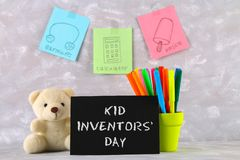 Teddy bear, markers, plaque and drawings of children's inventions - popsicles, Earmuffs, calculator on a gray background. Text -. Kid Inventors' Day Stock Photo