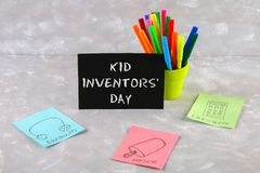 Teddy bear, markers, plaque and drawings of children's inventions - popsicles, Earmuffs, calculator on a gray background. Text -. Kid Inventors' Day Stock Photos