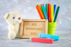Teddy bear, markers, plaque and drawings of children`s inventions - popsicles, Earmuffs, calculator on a gray background. Text -. Kid Inventors` Day Royalty Free Stock Images