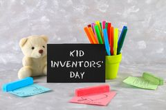 Teddy bear, markers, plaque and drawings of children's inventions - popsicles, Earmuffs, calculator on a gray background. Text -. Kid Inventors' Day Stock Photography