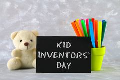 Teddy bear, markers, plaque and drawings of children's inventions - popsicles, Earmuffs, calculator on a gray background. Text -. Kid Inventors' Day Royalty Free Stock Photo