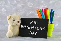 Teddy bear, markers, plaque and drawings of children's inventions - popsicles, Earmuffs, calculator on a gray background. Text -. Kid Inventors' Day Royalty Free Stock Photos