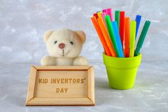 Teddy bear, markers, plaque and drawings of children's inventions - popsicles, Earmuffs, calculator on a gray background. Text -. Kid Inventors' Day Stock Image