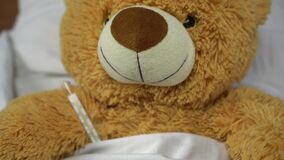 A teddy bear measures the temperature with a mercury thermometer. The bear lies in bed.